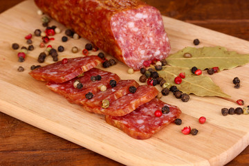 Tasty sausage on chopping board on browm background