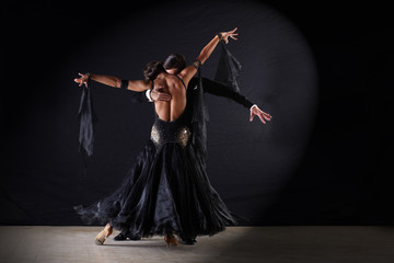 Wall Mural - Latino dancers in ballroom against on black background