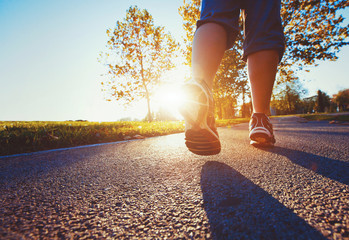fitness background, close up of runner feet on the road