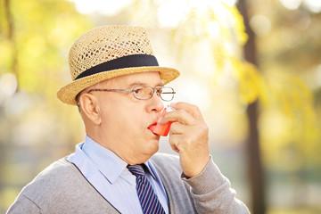 Senior gentleman taking asthma treatment in a park