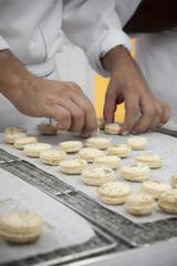 Chef adjust row of macaroon on tray