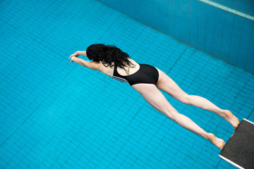 Schwimmerin springt von einem Sprungturm in Badeanstalt