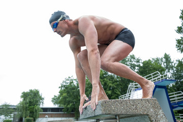 Schwimmer auf Startblock bei Wettkampf