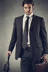 Successful businessman posing with umbrella