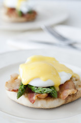 eggs Benedict with crispy bacon and asparagus.