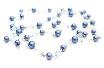 Blue, shiny necklace for the woman on white background