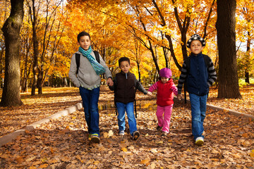 Wall Mural - Group of kids walk in autumn park