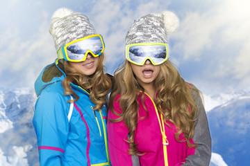 Two beauty smiling women in winter in mountains