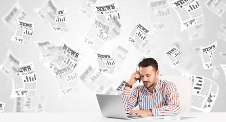 Business man at desk with stock market newspapers