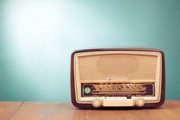 Old retro radio with green eye light on table
