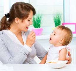 Wall Mural - Mother Feeding Her Baby Girl with a Spoon