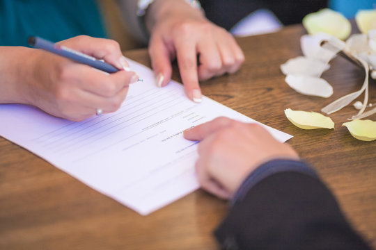 Closeup of Female Hand Signing Wedding Contract