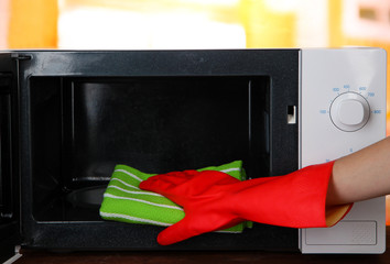 Hand with microfiber cleaning  microwave oven,