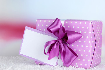 Gift box with blank label on carpet on bright background