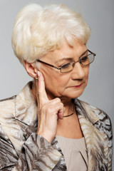An old woman touching her face, worried.
