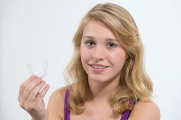 Jugendliche zeigt lächelnd Zahnspange