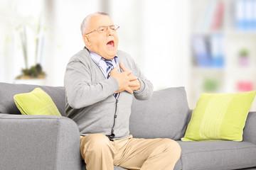 Senior man seated on sofa having a heart attack at home
