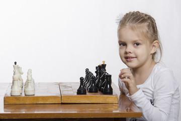 четырехлетняя девочка учится играть в шахматы