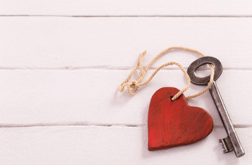 Old  key with a heart on white wood