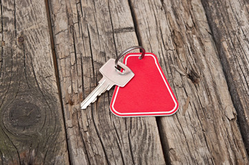 key with a blank label on an old wooden plank