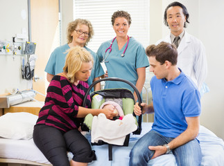Successful Medical Team With Newborn Baby And Parents In Hospita