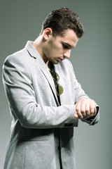 Handsome young businessman looking at his watch
