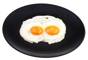 fried eggs on ceramic black plate