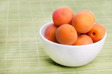 Apricots on board for cutting on napkin on wooden table