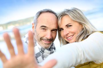 Senior couple showing hands towards camera