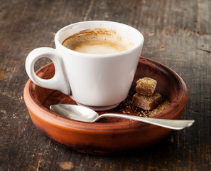 Cup of espresso coffee with brown sugar on dark background