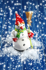Beautiful snowman  on blue wooden background