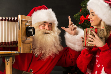 Photo of Santa Claus with his wife taking pictures with Christma
