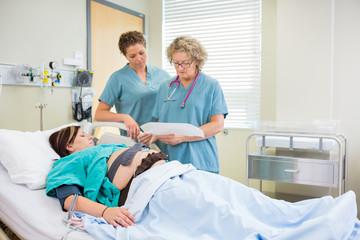 Nurses Inspecting Fetal Monitor Report