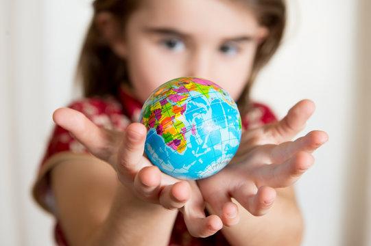 Cute lgirl holding little World Globe on her Hands