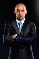 Portrait of a serious businessman on black background