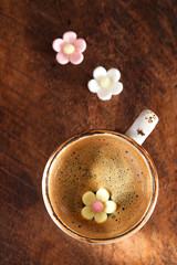 A cup of espresso coffee with sugar flowers, rustic style