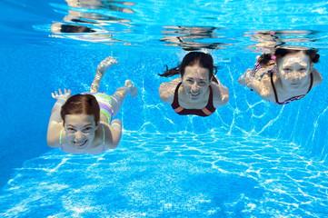 Happy family swim underwater in pool and having fun