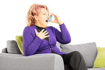 Mature woman seated on a sofa taking  treatment with inhaler