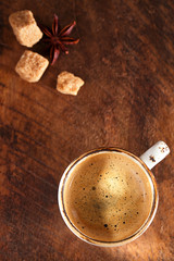 A cup of spiced coffee with anise star  and sugar