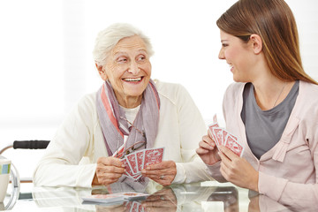 Senior woman playing cards with caregiver