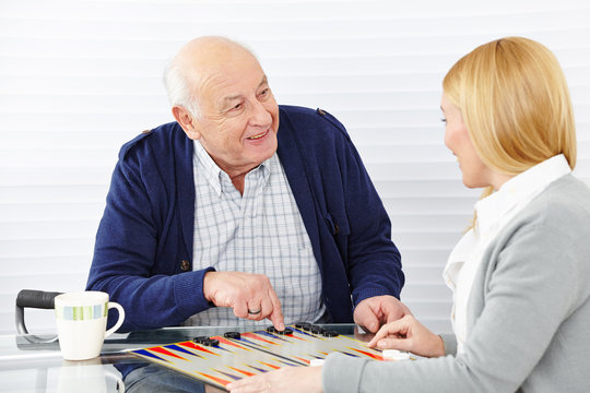 Woman playing backgammon with senior citizen