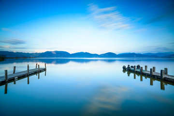 Two Wooden pier or jetty and on a blue lake sunset and sky refle