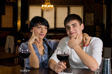 Couple sitting at the bar drinking red wine