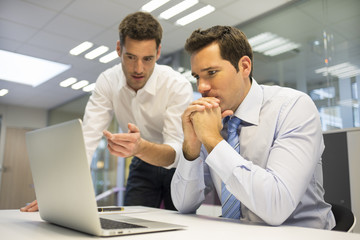 Two handsome businessmen working together on a project , office