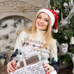 Beautiful girl at the fireplace with New Year's gifts