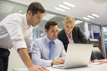 A business team of three in office and planning work