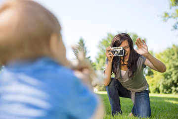 Mother Photographing Son Through Camera