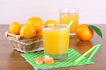 Glasses of fresh juice of tangerines and tangerines in a basket