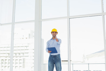 Architect in hard hat with clipboard gesturing thumbs up in offi