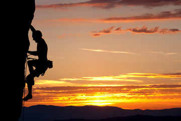 silhouette of climber on rock face